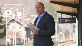 Ferrocarril disponible de la llegada del tren de With Newspaper del hombre de negocios que espera fotografía de archivo