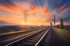 Ferrocarril en el movimiento en la puesta del sol Ferrocarril borroso imagen de archivo