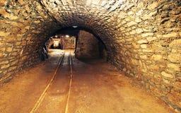 Ferrocarril subterráneo del túnel del oro de la mina Imagenes de archivo