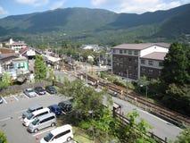 Ferrocarril, tren rojo, aparcamiento, edificio y calles en el campo japonés Imagenes de archivo