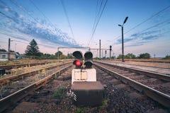 Ferrocarril y semáforo en la puesta del sol colorida Ferrocarril Foto de archivo libre de regalías