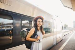 Ferrocarril y viaje del tema Mujer caucásica joven del retrato con la sonrisa dentuda que se coloca en el fondo del tren de la es imagen de archivo libre de regalías