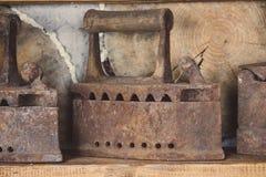 Ferros oxidados velhos na prateleira Ferramentas dom?sticas retros Ferros do vintage Ferros de alisamento oxidados imagens de stock royalty free