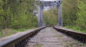 Ferrovia abbandonata nel legno attraverso il fiume Fotografia Stock