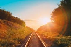 Ferrovia che passa avanti diritto con l'estate Hilly Meadow To Suns Fotografie Stock Libere da Diritti