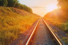 Ferrovia che passa avanti diritto con l'estate Hilly Meadow To Sunset Immagini Stock Libere da Diritti