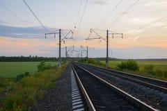 ferrovia con i pali nel evenin di estate fotografie stock libere da diritti