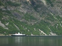 Ferry. A small ferry on the river passing by mountain Royalty Free Stock Image