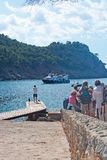 Ferry arrival and waiting tourists. CALA TUENT, MALLORCA, SPAIN - MAY 15, 2017: Ferry arrival and waiting tourists on a sunny day on May 15, 2015 in Cala Tuent Stock Photography
