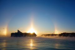 Ferry arriving to Helsinki harbor on a cold morning with winter halo on background Stock Images