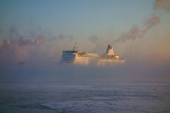 Ferry  arriving to Helsinki harbor on a cold winter morning in the middle of sea smoke Royalty Free Stock Images