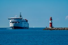 Ferry and beacon on the pier in Warnemuende stock photo