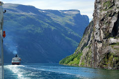 Ferry on blue water of Norwegian fjord. Royalty Free Stock Photography