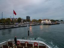 Ferry boat approaches to Kadikoy station. Cloudy fall rainy evening twilight outdoor shot royalty free stock image