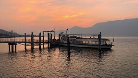 Ferry Boat arriving in the Harbor of Luino on the lake Maggiore at Sunset.