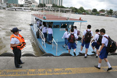 Ferry Boat on the Chao Phraya River in Bangkok. School children board a boat to cross the Chao Phraya River on September 14, 2011 in Bangkok, Thailand. The Chao Stock Photo