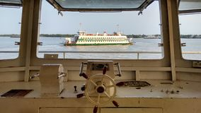 Ferry Boat Crossing Saigon River. View from the captain's bridge: White ferry boat crossing Saigon river at sunset Stock Photo