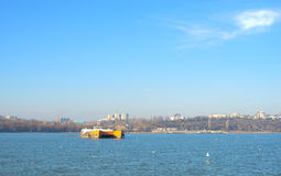 Ferry boat filled with people and cars crossing Danube River Stock Photo