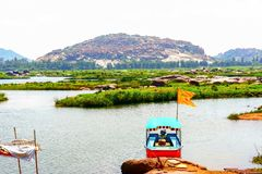 Ferry boat floating in the river in the backdrop of a stony hill royalty free stock photo