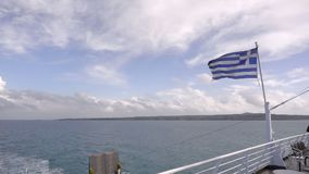 Ferry boat in Greece view on sea and waving national flag. Slow motion stock video footage