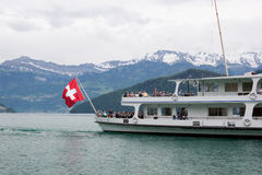 Ferry boat on Lake Lucerne. Lucerne, Switzerland June 6 2013: Ferry boat with flag flying carrying passengers on Lake Lucerne Royalty Free Stock Images