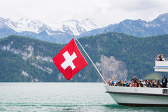 Ferry boat on Lake Lucerne. Lucerne, Switzerland June 6 2013: Ferry boat with flag flying carrying passengers on Lake Lucerne Stock Images