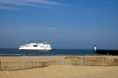 Ferry Boat leaving Calais, France. A ferry boat is heading from Calais, France to Dover, England. It is a warm summer day and you see the sandy beach. The Royalty Free Stock Photo
