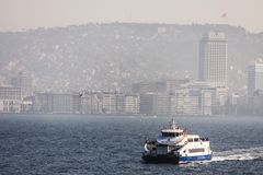 Ferry boat navigating in Izmir Turkey. A ferry boat is navigating on the sea in front of Izmir: the panorama of the city climbing the hills in a soft white fog Royalty Free Stock Photos