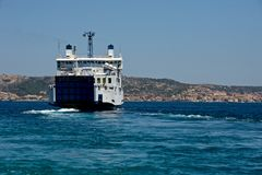 Ferry boat navigating in the middle of the sea. And La Maddalena coast in the background Stock Image