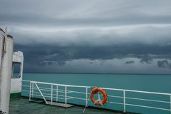 Ferry Boat with Orange Life-Buoy Ring Sail in Bad Weather with Thunderclouds. Marine Safety Concept.  royalty free stock photos
