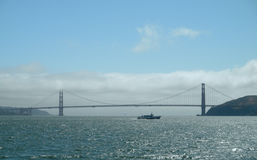 Ferry boat passes the Golden Gate bridge royalty free stock photography