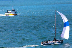 Ferry Boat and Sailboat. San Francisco, CA, USA - May 21, 2016: A sailboat and a passnger ferry boat cruising on the San Francisco Bay stock photo