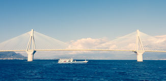 Ferry boat sailing under suspension bridge Royalty Free Stock Images