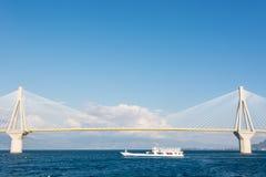 Ferry boat sailing under suspension bridge Stock Image