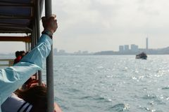 Passenger holds on to the handrail on the ferry boat. Ferry boat to Koh Larn island. Passenger holds on to the handrail on the ship. Cityscape of Pattaya City on stock images