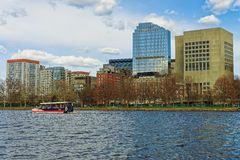 Boston skyline and ferry boat floating across the river. Ferry boat traveling across the river in the center of Boston, the United States. The city is located royalty free stock photos
