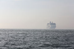 Ferry boat traveling in the distance at sea Stock Image