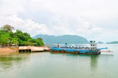 Ferry boat vessel for passengers and cars in Thailand. Ferry boat vessel for passengers and cars near small jetty with green islands on background Stock Photography