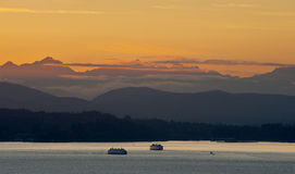 Ferry Boats and Olympic Mountains. During a beautiful sunset two Washington State Ferry boats make the crossing from Seattle to Bainbridge Island. The Olympic Royalty Free Stock Images
