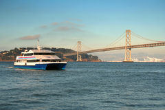 Ferry and bridge. Ferry crossing the bay with a suspension bridge on the background Royalty Free Stock Photos
