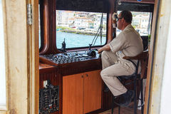 Ferry captain waits at the boat's controls Royalty Free Stock Photography