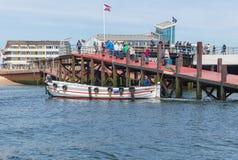 Ferry con i passeggeri che lasciano il porto Helgoland alla duna vicina dell'isola Fotografia Stock