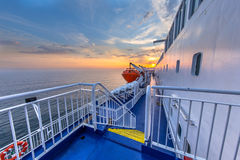 Ferry Deck staircase. Stairs and railing on Deck of Cruise ship liner sailing across the Northsea under beautiful sunset Royalty Free Stock Images