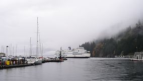 Ferry departing harbour on rainy day in West Vancouver, Canada. WEST VANCOUVER, CANADA - NOVEMBER 01, 2018: The double-ended ferry `Queen of Cowichan` departs stock video