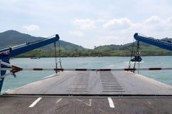 Ferry devant une île verte luxuriante Photographie stock