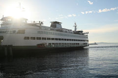 Ferry docked. A ferry is docked while sun rays pour over the ship Stock Photo