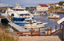 Ferry, fishing boats on the Norwegian harbor Stock Photos