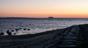 A ferry on the horizon at sunset. royalty free stock images