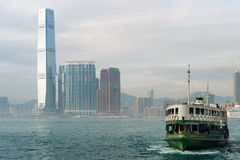 Ferry and International Commerce Centre (ICC) skyscraper in Hong Kong Stock Photos