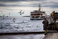 A ferry in Istanbul departing from port. Woman is standing near the water, watching and feeding the flying seagulls. stock image